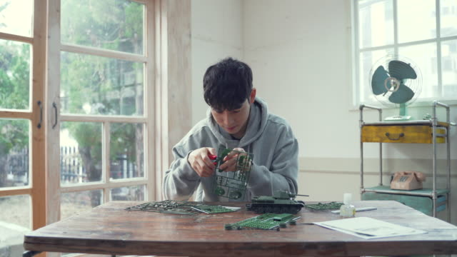 the man constructs figure toys in the home - sitting video stock e b–roll