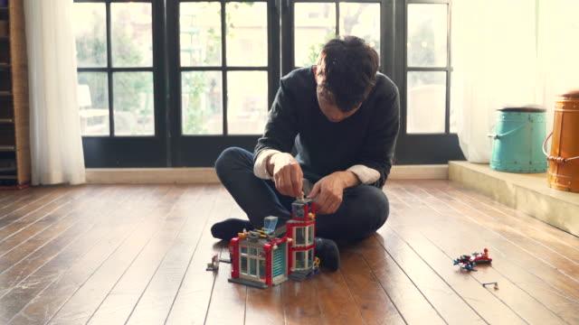 vídeos de stock, filmes e b-roll de the man constructs lego toys in the home - bloco de construção