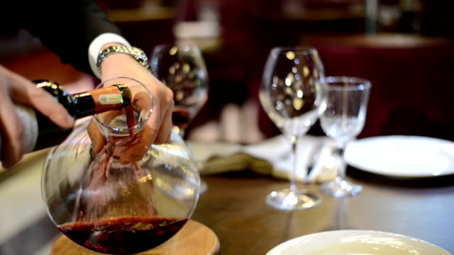 the man hand pouring the red wine from bottle  into the decanter - decanter stock videos & royalty-free footage