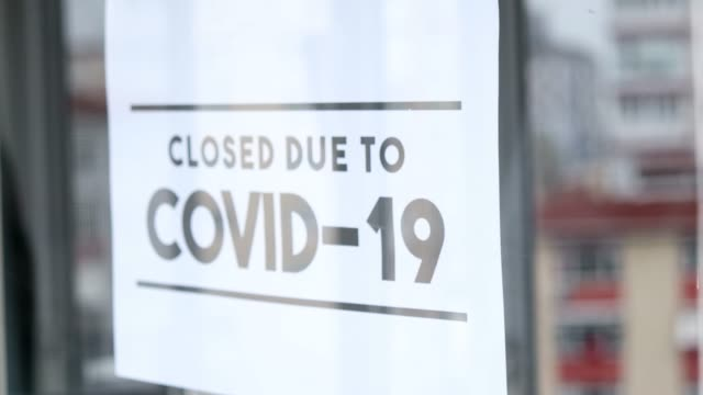 "the man hanging the sign ""closed due to covid-19"" on the glass of the shop because of the coronavirus. - crisis stock videos & royalty-free footage"