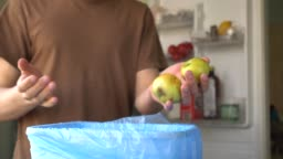 The man in the kitchen. Household waste of fresh fruit and vegetables in the garbage bin