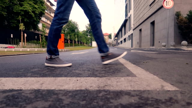 the man legs in grey shoes walk cross the street. close - up - human leg stock videos & royalty-free footage