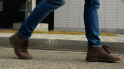 The man legs in shoes walk on the pavement closeup