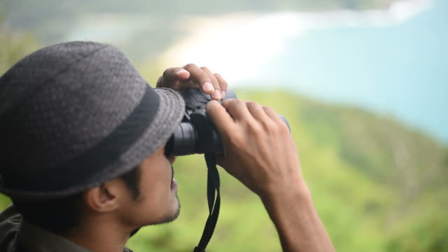 the man looking through binoculars on the mountain with seaview. - osservare gli uccelli video stock e b–roll