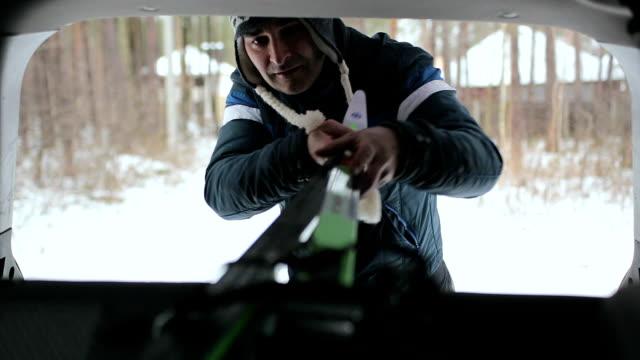vídeos de stock, filmes e b-roll de o homem coloca seus esquis dentro do carro. - equipamento esportivo
