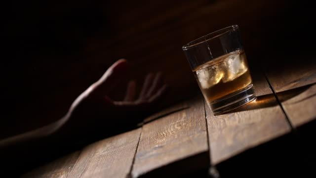 vidéos et rushes de l'homme prend un verre de boissons au whisky et tombe ivre. - glaçon