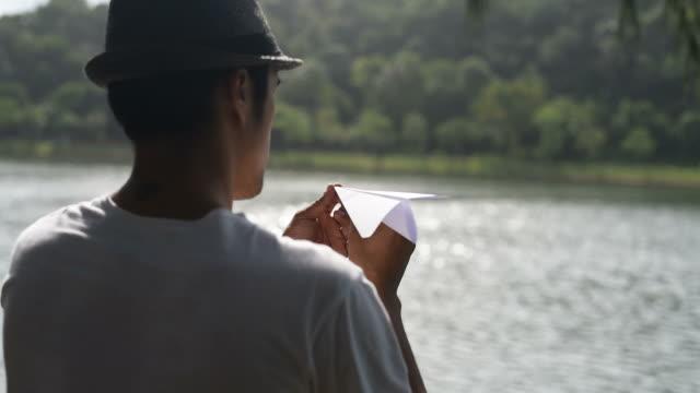 vídeos y material grabado en eventos de stock de el hombre lanza un avión de papel al lado del lago. - avión de papel