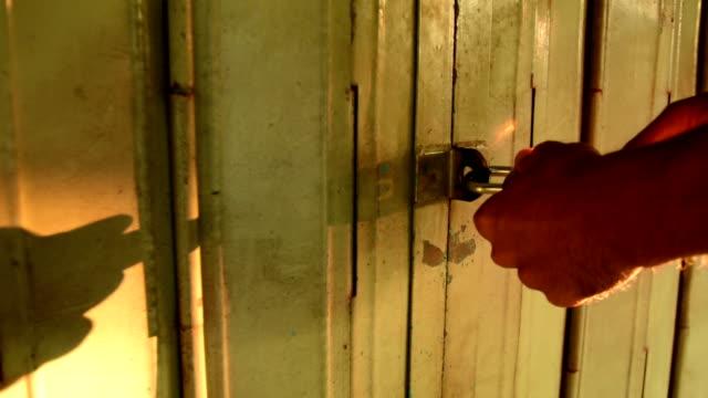 the man unlocked the entrance with the key. - aprire una serratura video stock e b–roll