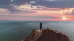 The man with bag standing on the mountain cliff on the seascape background