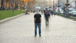 The man with medical face mask stands in the crowded city. time lapse