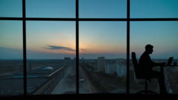 The man working near a panoramic window on a city background. time lapse