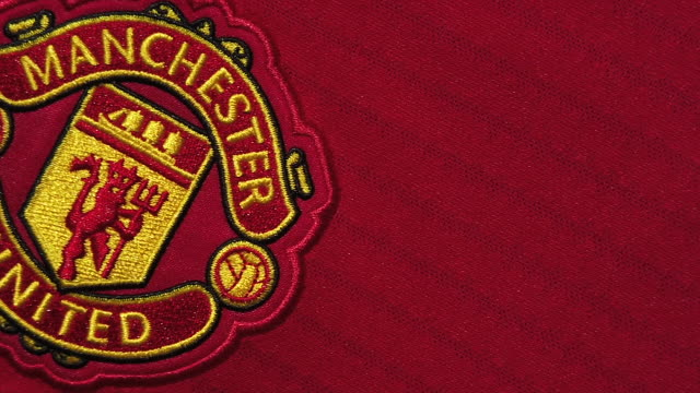the manchester united club crest on their home shirt on may 28 2020 in manchester england - バッジ点の映像素材/bロール