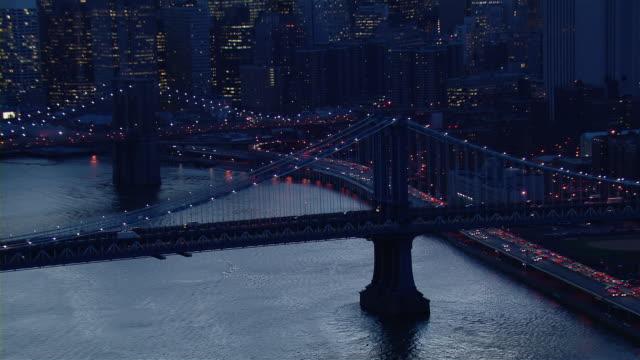 vídeos y material grabado en eventos de stock de the manhattan bridge and the brooklyn bridge illuminated at dusk in lower manhattan. - puente de brooklyn