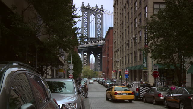 the manhattan bridge sits at the end of a busy brooklyn street in dumbo.  the empire states building is centered in the bottom arch. - international landmark stock videos & royalty-free footage