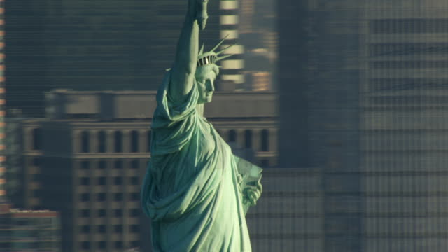 vidéos et rushes de the manhattan skyline forms a backdrop for the statue of liberty. - style néoclassique