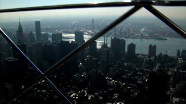 the manhattan skyline spreads beneath the observation deck of the empire state building. - observation point stock videos & royalty-free footage