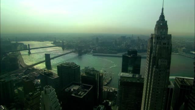 the manhattan skyscrapers border a series of bridges. - manhattan video stock e b–roll