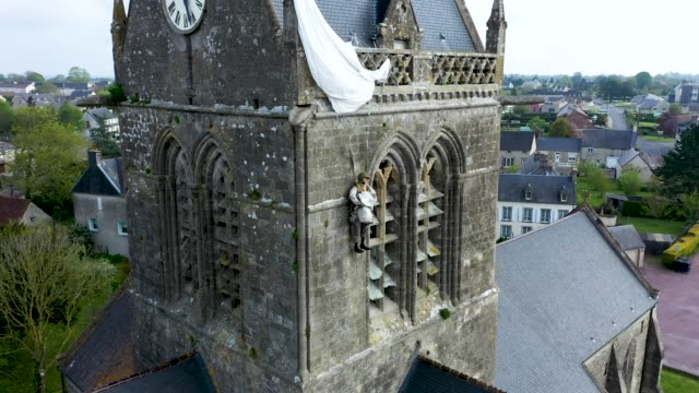 the mannequin of a us world war ii paratrooper hangs from a parachute from the church tower on may 1 2019 in saintemereeglise france the memorial... - d day stock videos & royalty-free footage