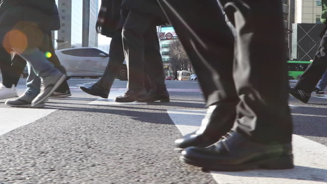 the man's shoes and walking on the crossroad in the city buildings - human leg stock videos & royalty-free footage