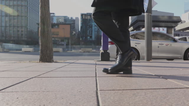 the man's shoes and walking on the street in the city buildings - side view stock videos & royalty-free footage