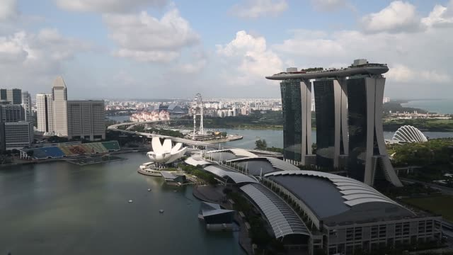 the marina bay sands hotel and casino right stands in singapore on thursday feb 18 the artscience museum foreground left and the singapore flyer... - singapore flyer stock videos and b-roll footage