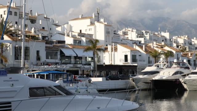 The marina of Puerto Banus of Marbella in Andalusia in Spain with a lot of expensive boats in the background the promenade and the beautiful...