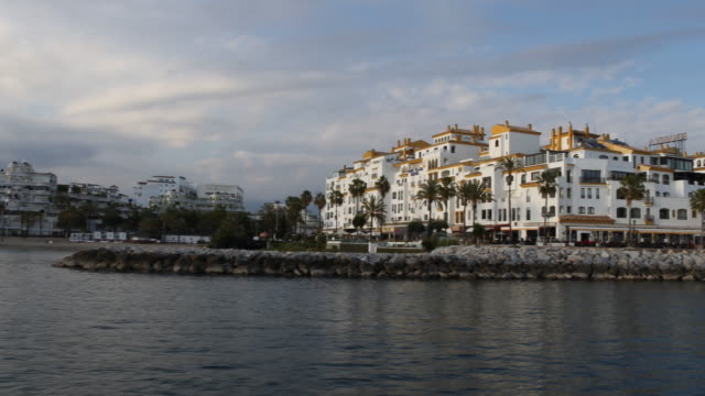 The marina of Puerto Banus of Marbella in Andalusia in Spain with a lot of expensive boats and expensive shops can be seen captured from a leaving...