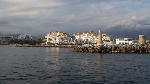 The marina of Puerto Banus of Marbella in Andalusia in Spain with a lot of expensive boats and the lighthouse can be seen captured from a leaving...