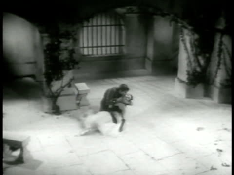 vidéos et rushes de the masked stranger taking off mask bending down to cradle kiss the woman ha ws trying to revive her ballet lifting carrying her over his shoulder... - 1952