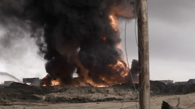 the massive black smoke cloud of a oil well set on fire by the islamic state in qayyarah, iraq - isis stock-videos und b-roll-filmmaterial