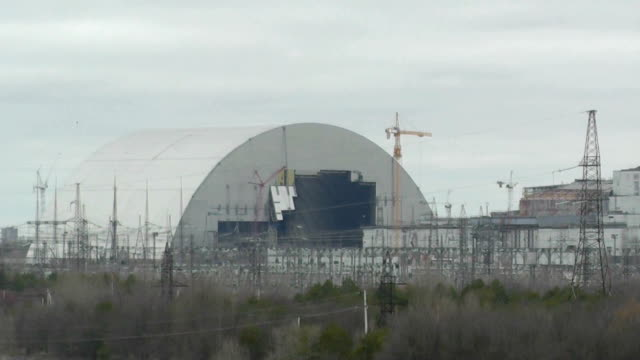 stockvideo's en b-roll-footage met the massive dome now being constructed at the stricken nuclear plant here shows the long time it takes to decommission reactors damaged in... - kernramp van tsjernobyl