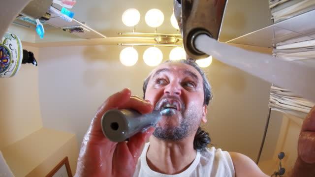 vídeos de stock, filmes e b-roll de os maduros, 45 anos, cabelos longos de velho escovar os dentes. - domestic bathroom