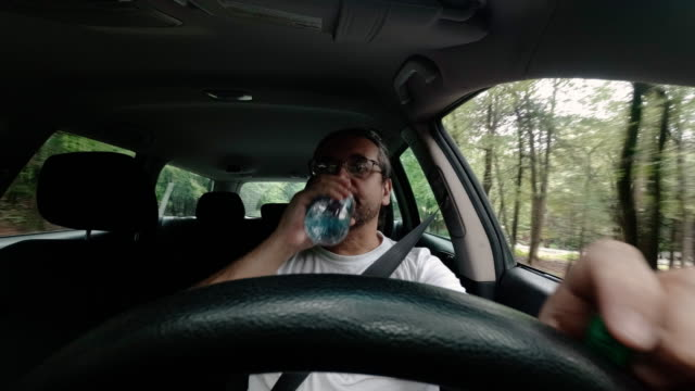 the mature 45-years-old caucasian man drinking water from a bottle when he driving a car in the community. accelerated timelaps-style video footage. - 45 49 anni video stock e b–roll