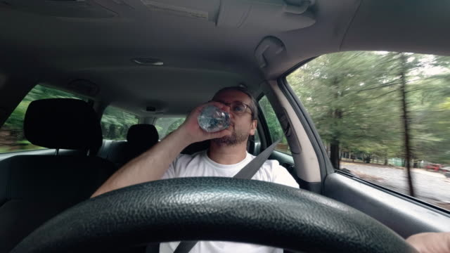 the mature 45-years-old caucasian man drinking water from a bottle when he driving a car in the community - 45 49 anni video stock e b–roll