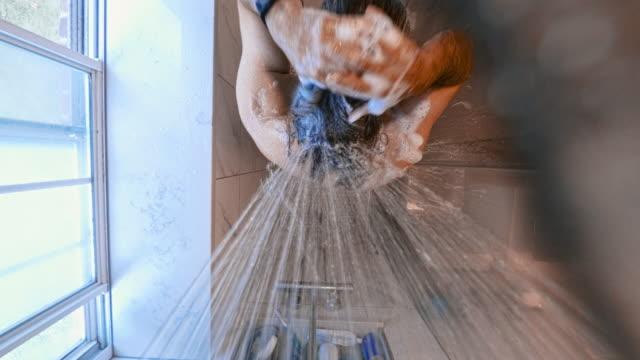 vídeos de stock, filmes e b-roll de o 45 anos de idade longo-haired homem maduro tomando uma ducha no banheiro, lavar a cabeça com um xampu. - espuma