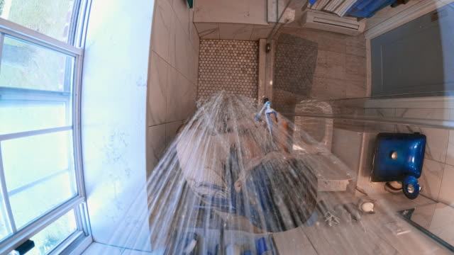 the mature 45-years-old long-haired man taking a shower in the bathroom - 45 49 anni video stock e b–roll