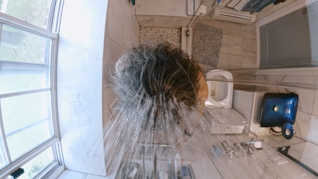 the mature 45-years-old long-haired man taking a shower in the bathroom - turning water on. - 45 49 anni video stock e b–roll
