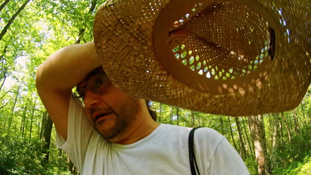 the mature, 45-years-old, long-haired man wearing the straw hat, walking in the forest in poconos, pennsylvania, in a hot sunny summer day. - 45 49 anni video stock e b–roll