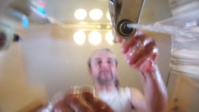 vídeos de stock, filmes e b-roll de o homem maduro, 45 anos, cabelos longos, barba por fazer, lavar o rosto e as mãos. - domestic bathroom