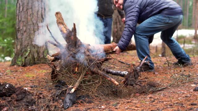 l'uomo maturo di 45 anni e suo padre, l'anziano attivo di 70 anni, fanno fuoco nella foresta invernale. - 45 49 anni video stock e b–roll