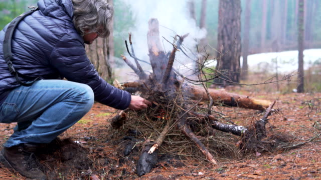 the mature 45-years-old man and his father, the active 70-years-old senior, make fire in the winter forest. - 45 49 anni video stock e b–roll