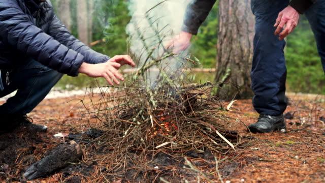 l'uomo maturo di 45 anni che riscalda le mani vicino al falò e suo padre, l'anziano attivo di 70 anni, fanno fuoco nella foresta invernale. - 45 49 anni video stock e b–roll