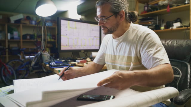 the mature, 50-years-old caucasian long-haired man working with architectural drawings in the home office located in a basement, making notes on drawings and comparing the info with some on the smartphone - engineer stock videos & royalty-free footage
