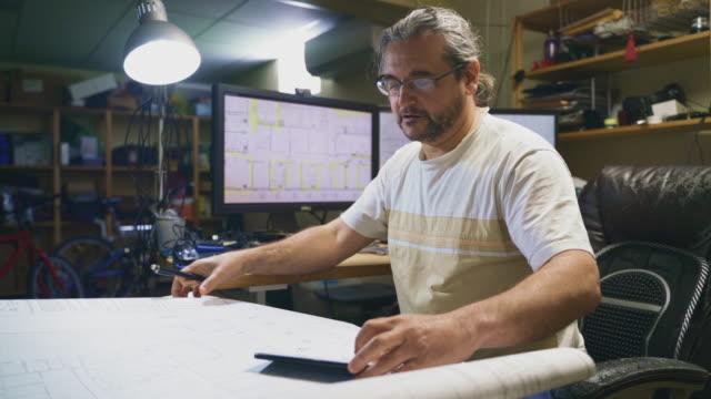 stockvideo's en b-roll-footage met de volwassen, 50-jarige kaukasische langharige man die werkt met architectonische tekeningen in het kantoor aan huis gelegen in een kelder, het maken van notities op tekeningen en het vergelijken van de info met een aantal op de smartphone - 50 54 years