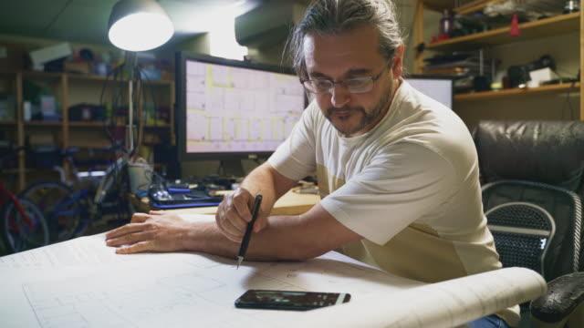 der reife, 50-jährige kaukasische langhaarige arbeitet mit architekturzeichnungen im home office in einem keller, macht notizen zu zeichnungen und vergleicht die informationen mit einigen auf dem smartphone - 50 54 years stock-videos und b-roll-filmmaterial