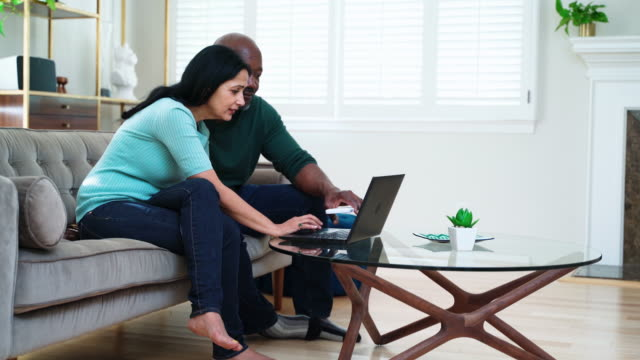 the mature couple sitting together on a couch and using a pc laptop for online shopping or video call via the internet. - 50 59 years stock videos & royalty-free footage
