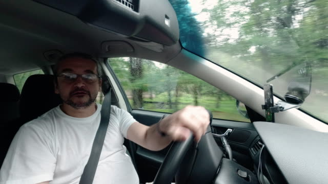 the mature handsome 45-years-old caucasian man driving the car - 45 49 anni video stock e b–roll