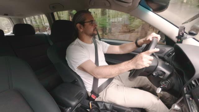中年のハンサムな 45 歳白人男性は、車を運転 - シートベルト点の映像素材/bロール