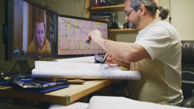 der reife mann arbeitet im homeoffice mit architekturzeichnungen und hat eine videokonferenz mit seiner kollegin - mitarbeiterin, einer frau mittleren alters. verwenden einer webcam, um die zeichnung dem kollegen anzuzeigen. - 50 54 years stock-videos und b-roll-filmmaterial
