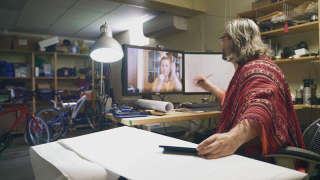 der reife mann arbeitet im homeoffice mit architekturzeichnungen und hat eine videokonferenz mit seiner kollegin - mitarbeiterin, einer frau mittleren alters. - 50 54 years stock-videos und b-roll-filmmaterial